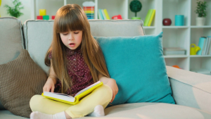 videoblocks-pretty-little-girl-reading-interesting-book-while-sitting-on-the-couch-in-lotus-position-in-the-living-room_hwzvmdthbz_thumbnail-full01